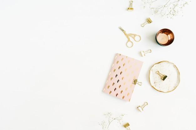 Moderner home-office-schreibtisch im goldstil mit notizbuch, schere und clips auf weißer oberfläche