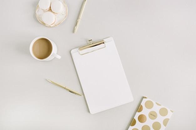 Moderner home-office-schreibtisch mit zwischenablage, makronen, stift, kaffeetasse auf pastellfarbenem hintergrund. flache lage, ansicht von oben