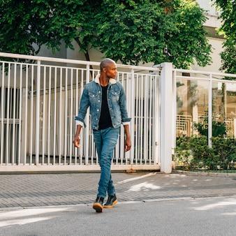 Moderner hübscher afrikanischer junger mann, der die straße kreuzt