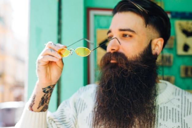 Moderner hübscher junger bärtiger mann, der in der hand gelbe brillen hält