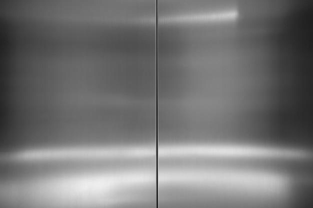 Moderner industrieller metallischer hintergrund. schließen sie herauf foto der aufzugstüren edelstahloberflächentextur mit glänzendem hellem licht, das auf oberfläche reflektiert wird