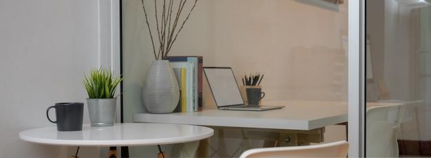Moderner innenbüroraum mit weißem kreis couchtisch neben weißem arbeitstisch
