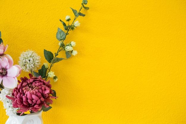 Moderner innenstil der gelben wand mit bunter blumenhintergrundbeschaffenheitsdekoration