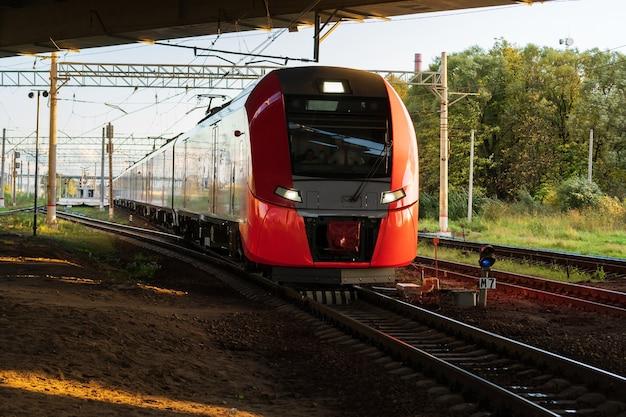 Moderner intercity-hochgeschwindigkeitszug unter der brücke bei sonnenuntergang kommerzieller vorortverkehr