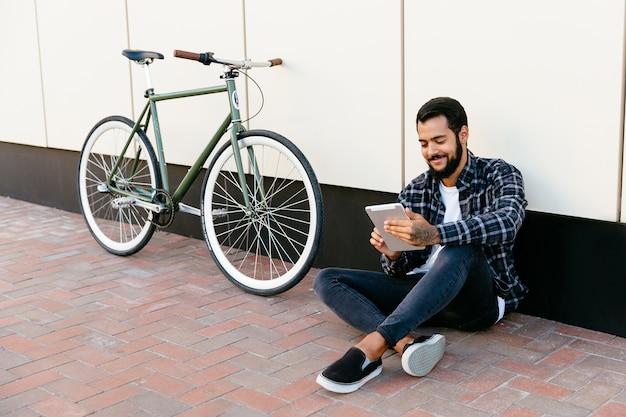 Moderner junger bärtiger mann, der eine digitale tablette, nett lächelnd verwendet