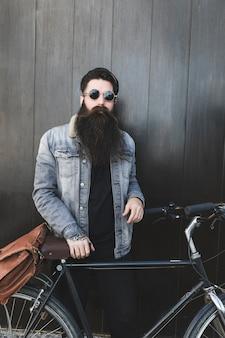 Moderner junger bärtiger mann, der mit fahrrad vor schwarzer hölzerner wand steht