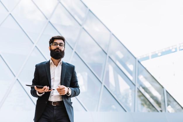 Moderner junger geschäftsmann, der vor dem unternehmensgebäude hält digitale tablette steht