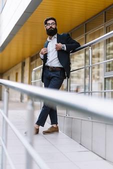 Moderner junger geschäftsmann mit dem langen bart, der vor unternehmensgebäude steht