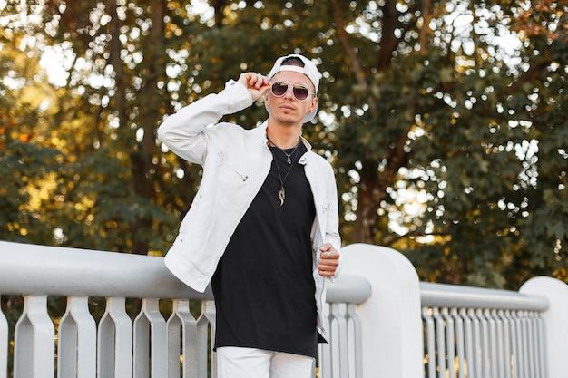 Moderner junger hipster-mann in einer weißen sommerjacke in der sonnenbrille in einem trendigen jeans-t-shirt wirft in einem park nahe einem metallzaun auf
