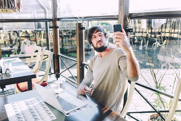 Moderner junger mann, der fotos von bei der arbeit macht.