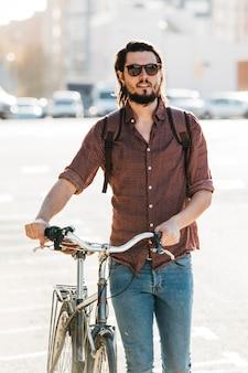 Moderner junger mann, der mit fahrrad auf straße geht