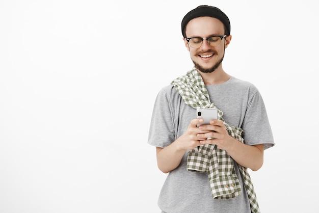 Moderner junger mann, der spaß hat, amüsante app im smartphone zu spielen
