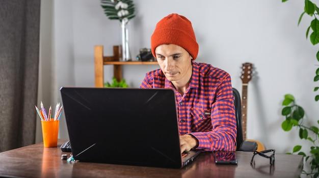 Moderner junger mann in einem rot karierten hemd und hut arbeitet an einem laptop