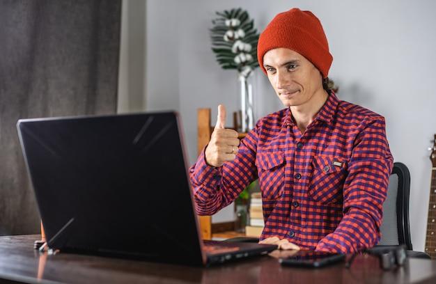 Moderner junger mann in einem rot karierten hemd und hut gibt einen daumen auf, als er auf den laptopbildschirm schaut
