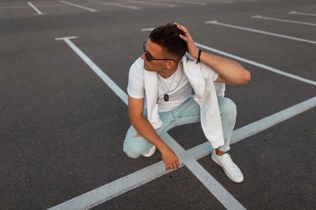 Moderner junger mann in sonnenbrille in vintage blue jeans in einem stilvollen weißen t-shirt in turnschuhen entspannt sich auf der straße. urbaner typ, der auf der straße ruht. sommerjugendmode. modische herrenmode.