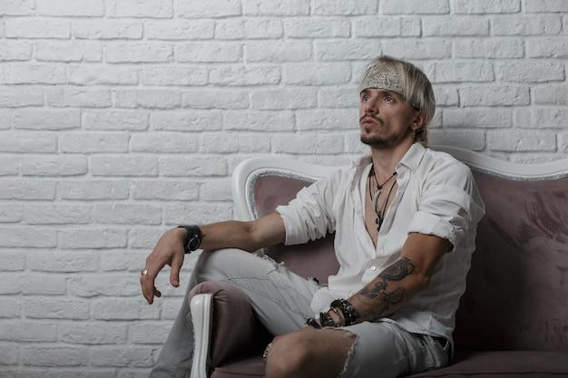 Moderner junger mann mit bart in einem grauen weinlesetuch mit einem tattoo in einem stilvollen weißen hemd in zerrissenen jeans entspannt sich sitzend auf einem weichen sofa