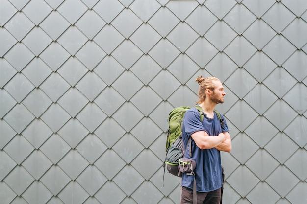 Moderner junger mann mit dem reiserucksack, der weg schaut