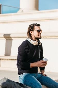 Moderner junger Mann mit Kopfhörer um seinen Hals, der Mitnehmerpapierkaffeetasse hält