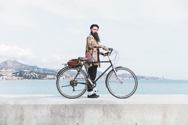 Moderner junger mann mit seinem fahrrad, das auf wellenbrecher nahe der küste steht
