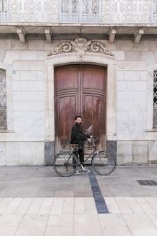 Moderner junger mann mit seinem fahrrad, das vor geschlossener tür steht