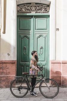 Moderner junger mann mit seinem fahrrad, das vor grüner tür steht