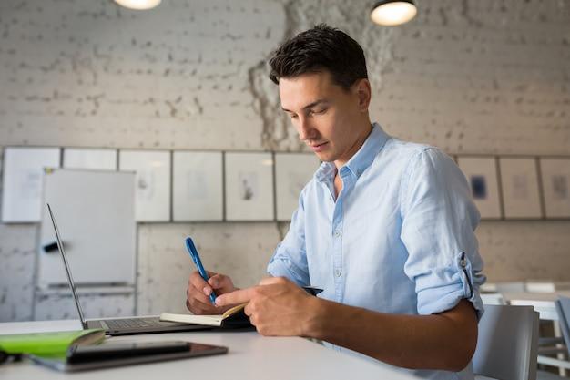 Moderner junger schöner mann, der denkt, notizen in notizbuch schreibt