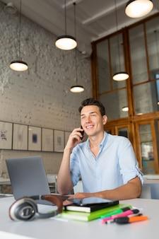 Moderner junger schöner mann, der im mitarbeitenden büro sitzt