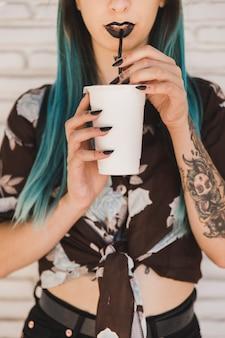 Moderner junger trinkender kaffee der frau mit stroh