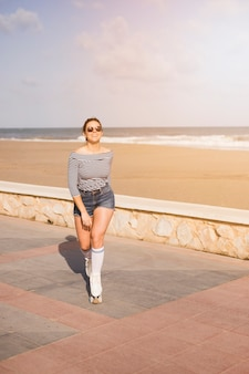 Moderner junger weiblicher schlittschuhläufer, der nahe dem strand geht