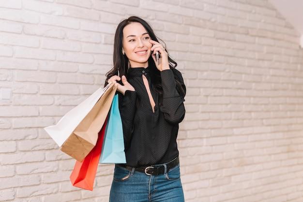 Moderner käufer mit den taschen, die am telefon sprechen