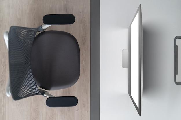 Moderner komfortabler arbeitsbereich - computertisch mit weißem computermonitor und orthopädischem stuhl. draufsicht. heimarbeit außerhalb des bürokonzepts.
