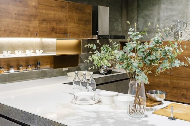 Moderner kücheninnenraum mit hölzernen fassaden und granit worktop und weißen schränken