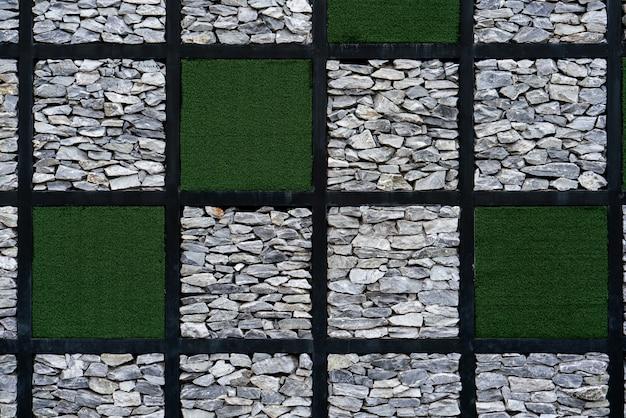 Moderner künstlicher gras- und steinwandhintergrund.