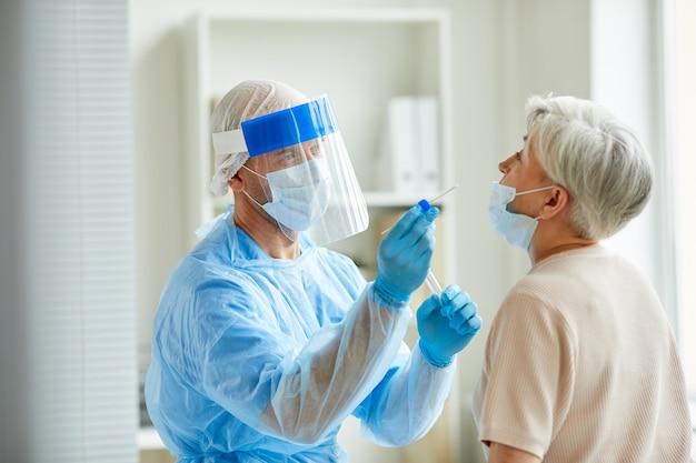 Moderner laborarbeiter, der persönliche schutzausrüstung trägt, die ältere frau auf coronavirus unter verwendung der nasentupfermethode prüft