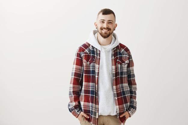 Moderner lächelnder kerl, der auf grau steht