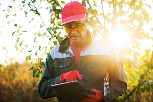 Moderner landwirt mit ausrüstung, die eine tablette betrachtet.