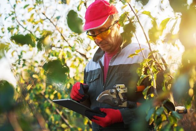 Moderner landwirt mit handschuhen und augenschutz, die eine tablette betrachten, während sie große schere halten.