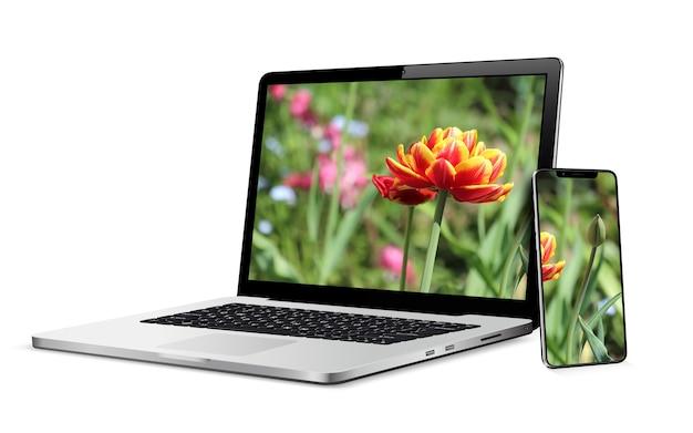 Moderner laptop-computer mit smartphone lokalisiert auf weiß