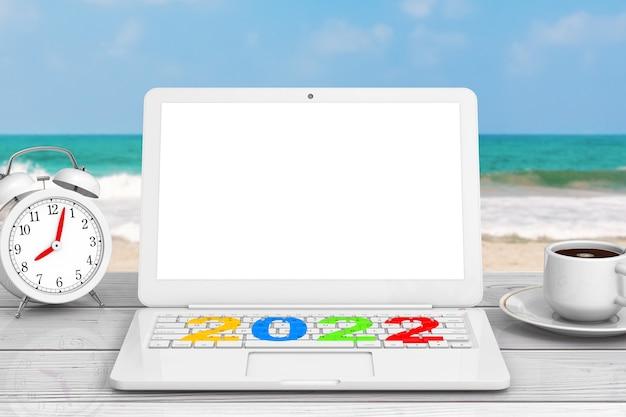 Moderner laptop mit neuem 2022-jahreszeichen, tasse kaffee und wecker vor extremer nahaufnahme des ozeans. 3d-rendering