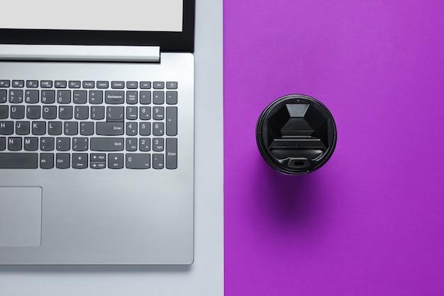 Moderner laptop, tasse kaffee auf grauem lila tisch. draufsicht. büro flach liegen