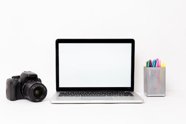Moderner laptop und kamera auf weißem hintergrund