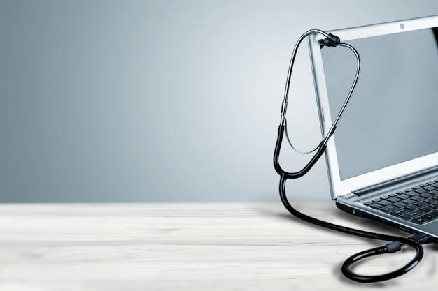 Moderner laptop und stethoskop im hintergrund, nahaufnahme
