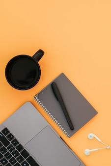 Moderner laptop, weiße kopfhörer, graues notizbuch mit einem stift und einer tasse kaffee auf der orangefarbenen oberfläche