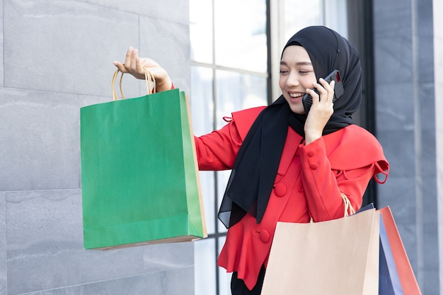 Moderner lebensstil der arabischen muslimischen jungen frau im schleier-hijab mit einkaufstüten, die auf der einkaufsstraße telefonieren.