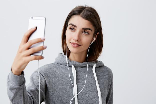 Moderner lebensstil. schließen sie herauf des schönen jungen brünetten kaukasischen mädchens im lässigen kapuzenpulli, der mit freund mit video auf smartphone spricht, kopfhörer tragend