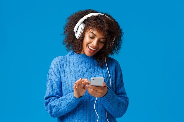 Moderner lifestyle, technologie und urbanes konzept. attraktive hippie-mädchen-afroamerikanerfrau in der winterstrickjacke, im afrohaarschnitt, in tragenden kopfhörern und in der mitteilung unter verwendung des smartphone, lächelnd
