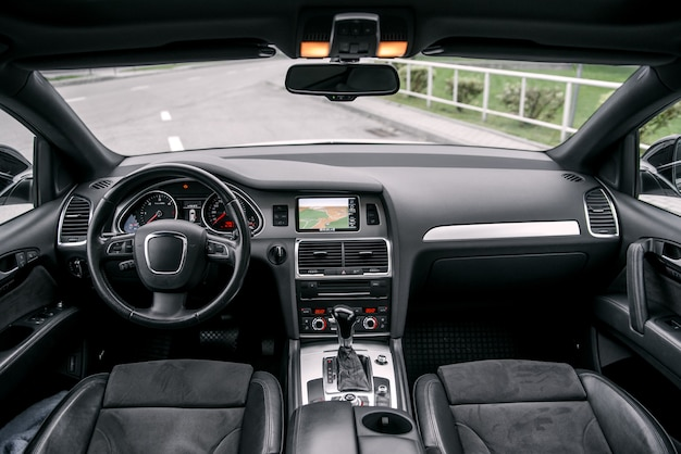 Moderner luxusprestigeautoinnenraum, armaturenbrett, lenkrad. innenausstattung aus schwarzem leder.