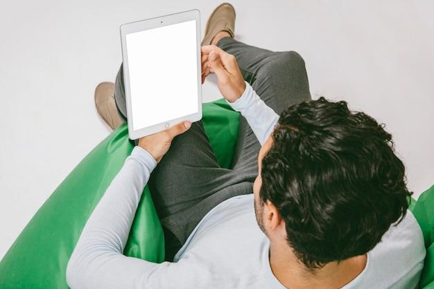 Moderner mann auf dem sofa mit tablette