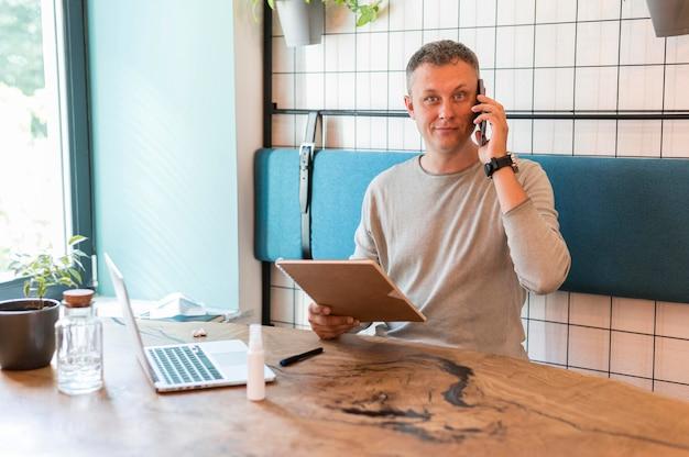 Moderner mann, der am telefon während der arbeit spricht