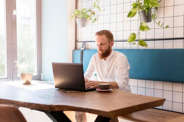 Moderner mann, der an seinem laptop arbeitet